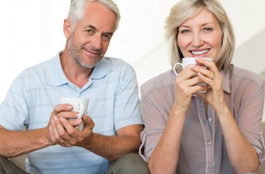 Smiling couple sipping mugs of soothing tea for pain relief
