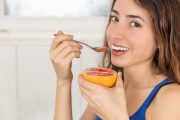 Woman on grapefruit diet eats a half of a grapefruit