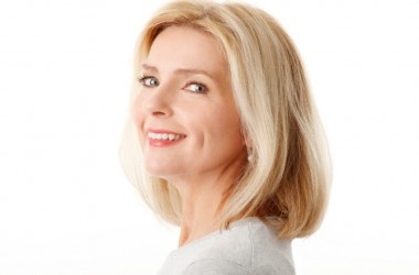 Close-up portrait of beautiful mature woman standing against white background.