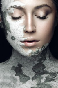 Woman with clay treament on her face and body