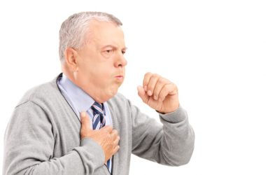 A mature man with gray hair coughs into his hand needs cough remedies