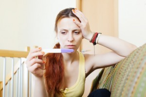 serious young woman sitting on sofa looking at pregnancy test results