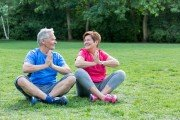 Mature man and woman who have overcome back and neck pain do exercise on grass in a park.