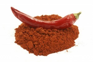 Red hot pepper sitting on a pile of chili powder