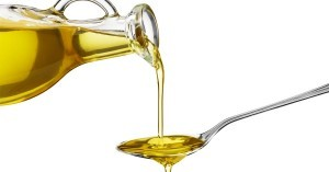High fat olive oil being poured from a glass jar onto a spoon