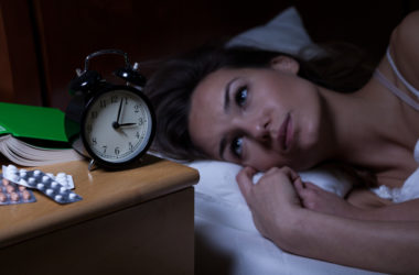 Woman can't fall asleep stares at clock