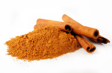 cinnamon powder and sticks on a white background