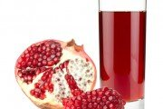 Pomegranate juice in glass and ripe pomegranate