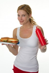 Woman about to put ketchup on her burgers