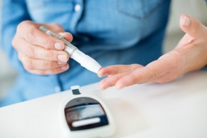 Diabetic woman sticking her finger to check her blood sugar levels