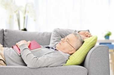 Senior man sleeping on gray sofa glasses on book open