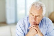 Close-up of serious senior man with hand on chin looking away at home. Horizontal shot.