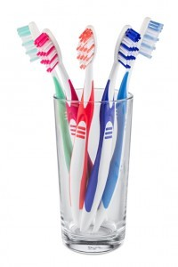 glass with colorful tooth brushes isolated on white background