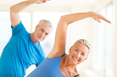 Portrait of smiling senior couple performing exercise to combat heart disease