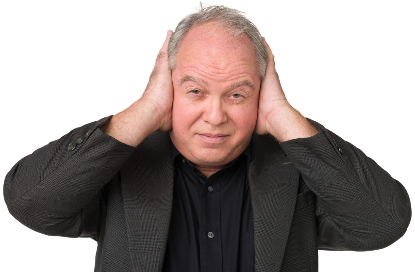 Mature man covering his ears