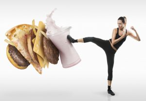 Woman kicking a stack of junk foods