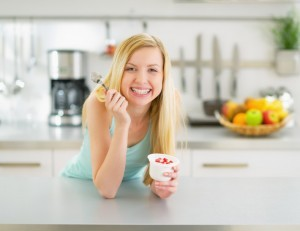 "Woman eating probiotic yogurt wondering ""How can I avoid yeast infections?"""