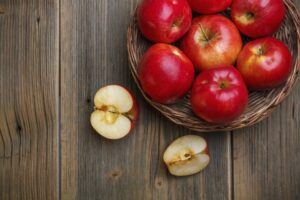 A basket of red apples on a wooden table