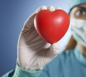 Gloved hand holding a heart shaped object