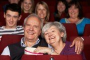 Senior Couple Watching Film Laughing In Movie Theater