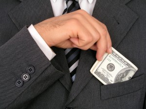 Close up of a man putting money into or taking money out of his suit pocket