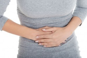 Woman suffering from constipation and belly ache holds stomach