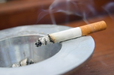 Burning cigarette in a white ashtray with smoke