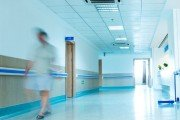 blurred figures wearing medical uniforms walking through the hallway in hospital