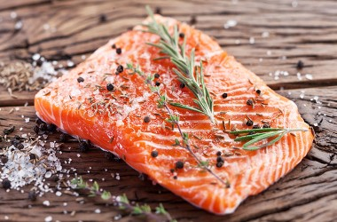 Salmon filet with healing herbs on a wooden carving board.