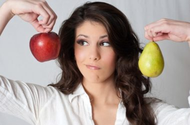 Woman holds up an apple and pear which could reduce stroke risk