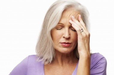 Woman holding head experiencing headache symptoms
