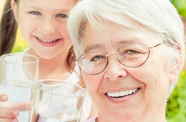 Smiiling grandmother and granddaughter drink water