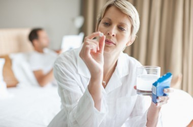 Woman holding antibiotic or probiotic pill