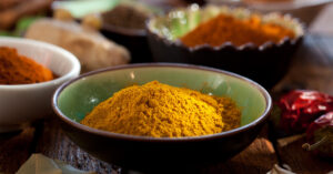 Dishes filled with fresh ground spices with orange turmeric in the front