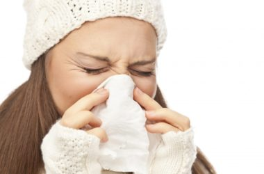 Woman with a cold or the flu wearing a white winter hat and sneezing into a tissue