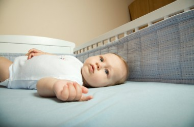Baby in crib with a crib bumper in background