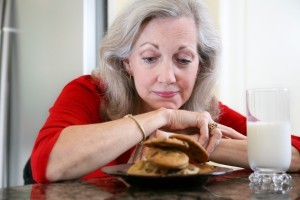 Mature diabetic woman fights sugar cravings as she looks longingly a cookies