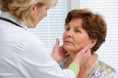 Female doctor performin a thyroid exam in the office