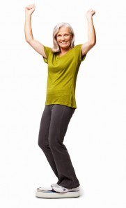 Full length portrait of happy senior woman standing on bathroom scale with hands raised.