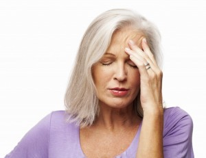 Woman feeling tired and fatigued holds her head