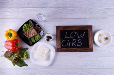 "Low carb diet foods on table with a small chalkboard with words ""low carb"" written on it"