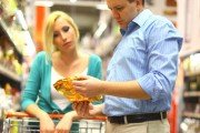 Couple reading food labels in the grocery store looking for additives.