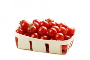 cherry tomatoes in basket isolated on white