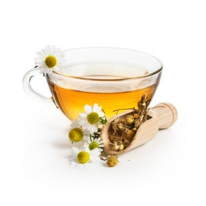 Herbal tea with chamomile flowers on white background