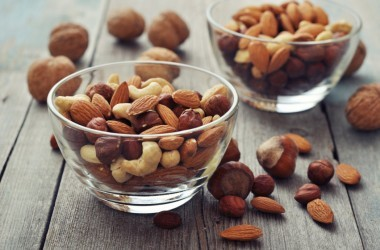 Almonds, walnuts, cashew and hazelnuts in glass bowls on wooden background good for heart health