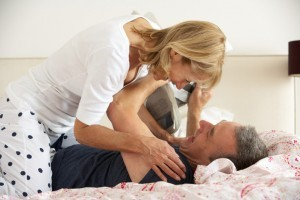 Senior Couple Fooling Around Together In Bed Whilst Man Reads Newspaper