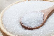 Hidden sugar which is linked to high blood pressure other health problems on a spoon