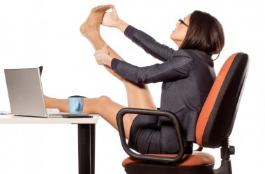 Woman with plantar fasciitis foot pain mssaging foot at desk