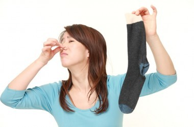 Woman trying to not smell stinky sock from foot odor, stinky feet.