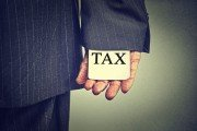 Close up of business man with tax sign up his sleeve